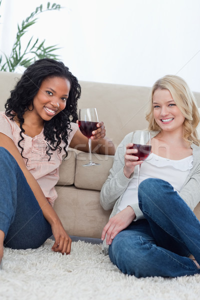 Two women sitting on the ground holding wine glasses are smiling at the camera Stock photo © wavebreak_media