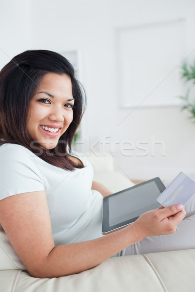 Woman smiling while holding a card and a tactile tablet in a living room Stock photo © wavebreak_media