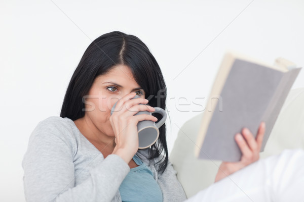 Woman drinking from a grey mug while reading a book in a living room Stock photo © wavebreak_media