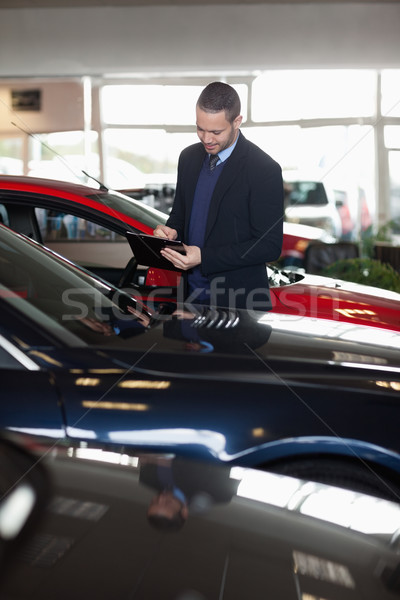 Man writing on a notepad in a garage Stock photo © wavebreak_media