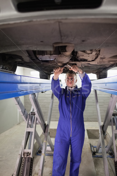 Mechanic standing while repairing the below of a car in a garage Stock photo © wavebreak_media