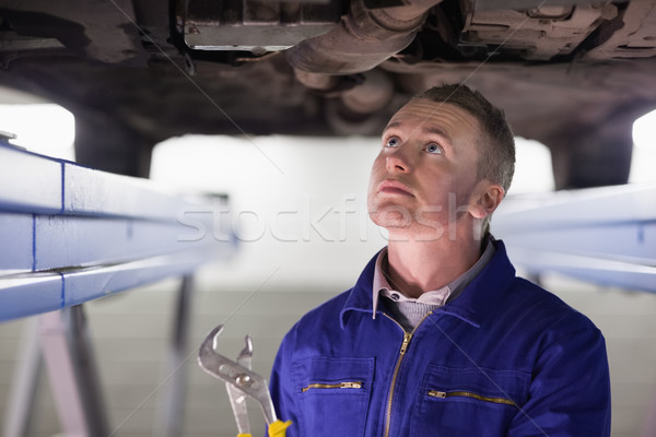 Mechanic looking at the below of a car while holding an adjustable pliers in a garage Stock photo © wavebreak_media