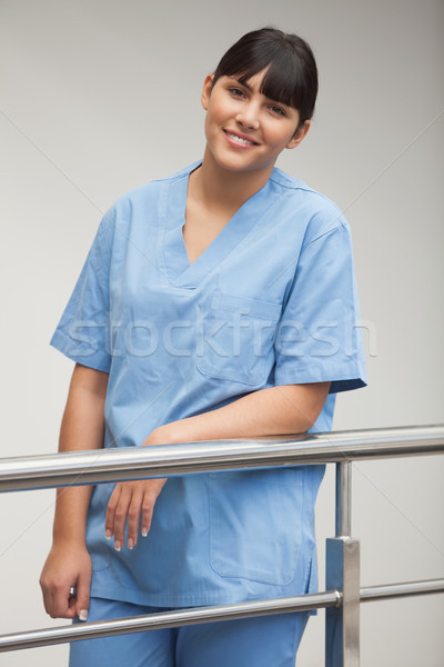 Nurse leaning while leaning against railing in hospital corridor Stock photo © wavebreak_media
