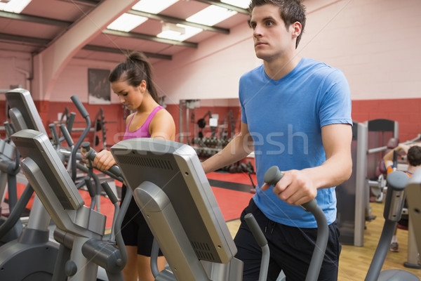 Woman and man stepping on step machines in gym Stock photo © wavebreak_media