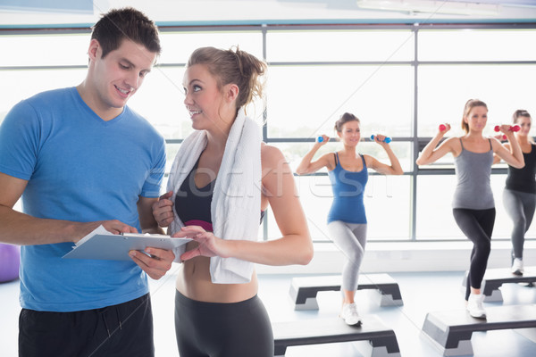 Trainer presenting timetable while aerobics class lifting weights in gym Stock photo © wavebreak_media