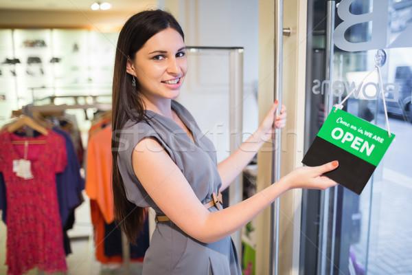 Vrouw opening kleding store deur teken Stockfoto © wavebreak_media
