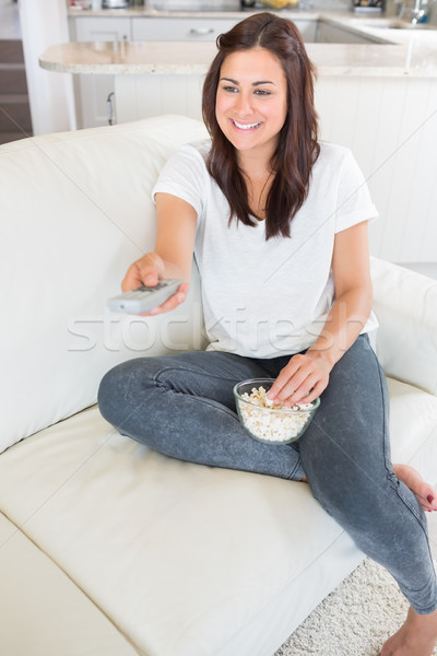 Woman watching tv and eating popcorn while holding a remote on sofa Stock photo © wavebreak_media