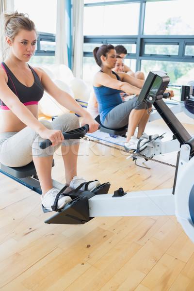 Man and womenusing the row machines in fitness studio Stock photo © wavebreak_media