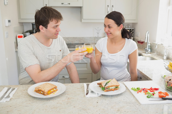 Two people eating sandwiches and drinking orange juice in the kitchen Stock photo © wavebreak_media
