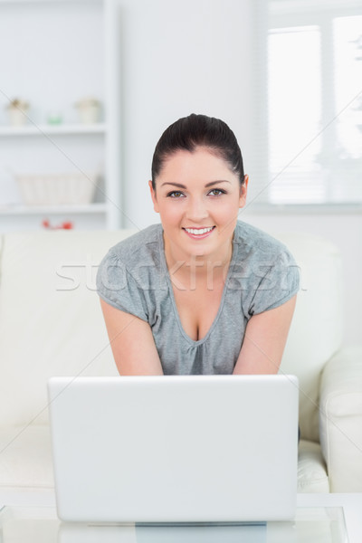 Young woman sitting on the couch in a living room while smiling and using a laptop Stock photo © wavebreak_media
