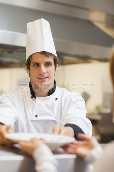 Chef passing plate to waitress at order station in kitchen Stock photo © wavebreak_media