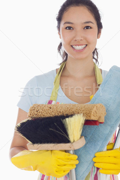 Smiling woman holding brushes and mops wearing apron and rubber gloves Stock photo © wavebreak_media