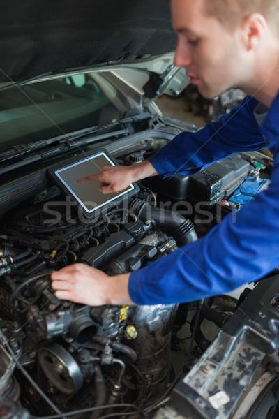 Mechanic with tablet pc repairing car Stock photo © wavebreak_media