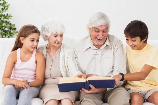 дедушка и бабушка чтение книга счастливым внучата диване Сток-фото © wavebreak_media