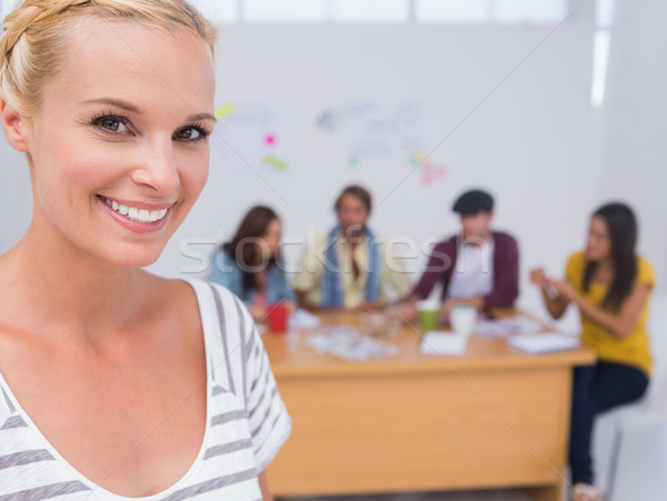 Stock photo: Prettty editor smiling at camera as team works behind her