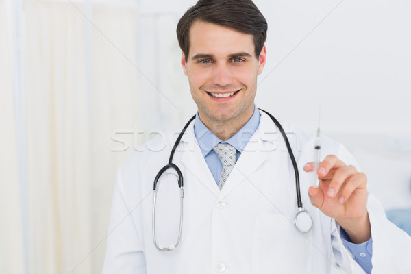 Portrait of a handsome doctor holding an injection Stock photo © wavebreak_media