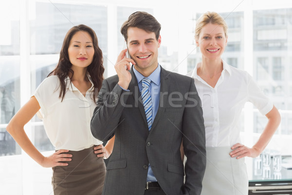Happy businessman on the phone in front of his team Stock photo © wavebreak_media