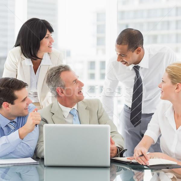 Happy business team gathered around laptop chatting Stock photo © wavebreak_media