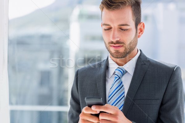 Handsome young businessman text messaging Stock photo © wavebreak_media