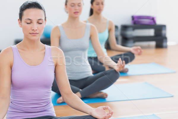 Women in lotus posture with eyes closed at fitness studio Stock photo © wavebreak_media