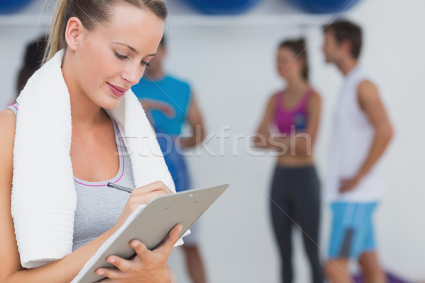 Trainer writing on clipboard with fitness class in background at Stock photo © wavebreak_media
