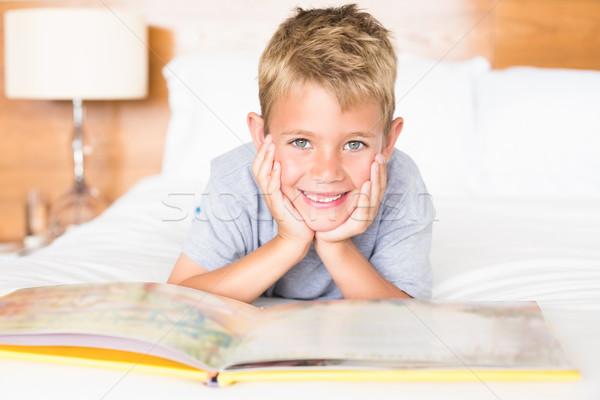 Smiling blonde boy lying on bed reading a storybook Stock photo © wavebreak_media