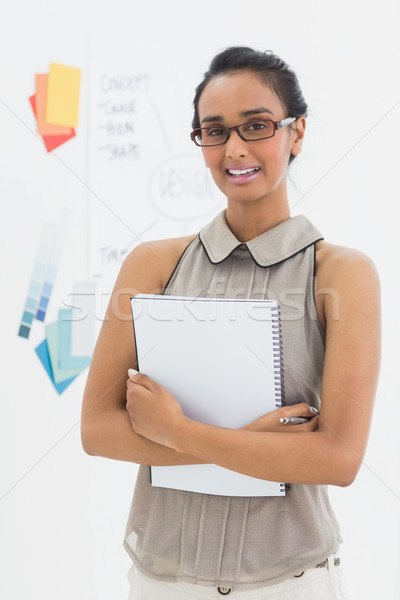 Stock photo: Designer holding notepad and smiling at camera