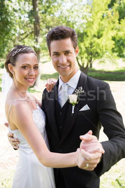 Happy newly wed couple dancing together in garden Stock photo © wavebreak_media