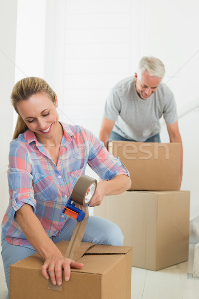 Happy couple sealing cardboard moving boxes Stock photo © wavebreak_media