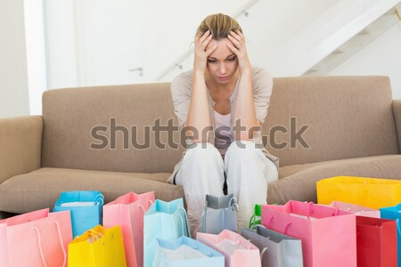 Regretful woman looking at many shopping bags on the couch Stock photo © wavebreak_media