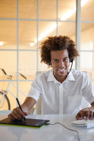 Casuale giovani imprenditore auricolare desk ufficio Foto d'archivio © wavebreak_media