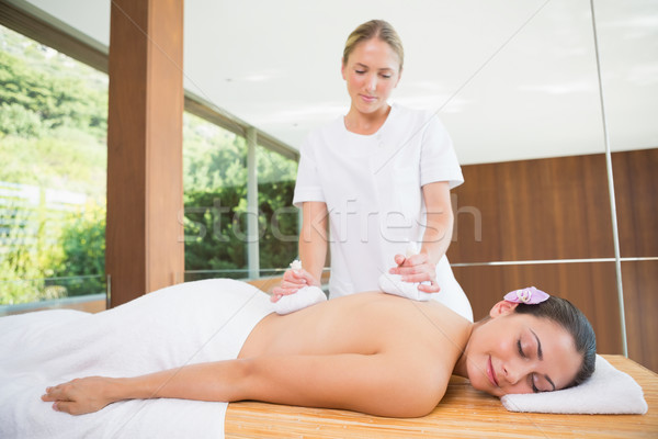 Smiling woman getting a back massage with herbal compresses Stock photo © wavebreak_media