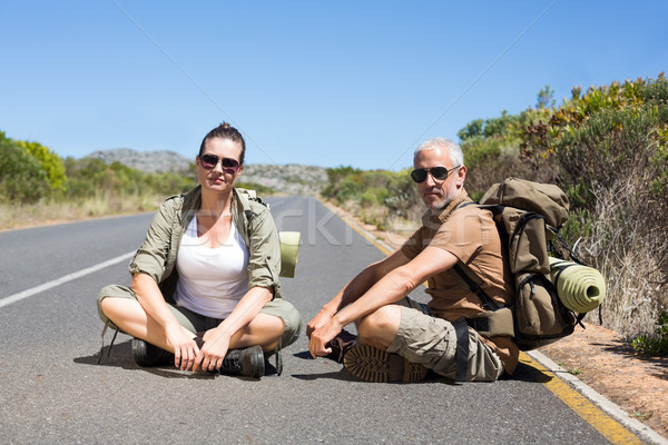 Hitch hiking couple sitting on the side of the road looking at c Stock photo © wavebreak_media
