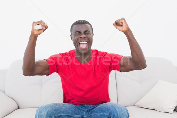 Fútbol ventilador rojo sesión sofá Foto stock © wavebreak_media