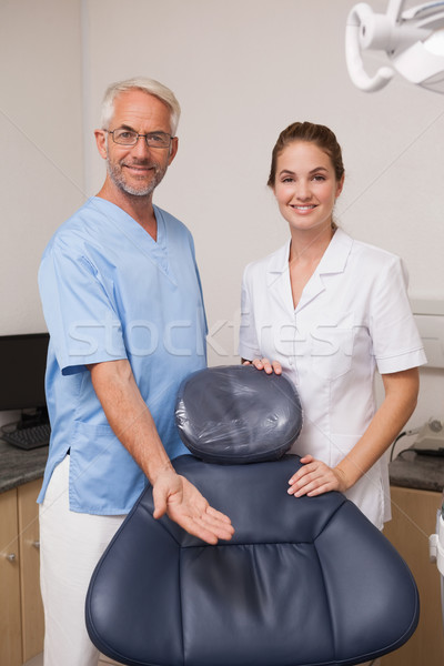 Dentist and assistant smiling at camera inviting you to the chai Stock photo © wavebreak_media