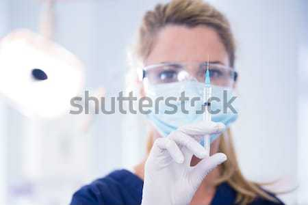 Dentist in surgical mask and dental loupes holding pliers over p Stock photo © wavebreak_media