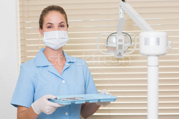 Dental assistant in blue holding tray of tools Stock photo © wavebreak_media