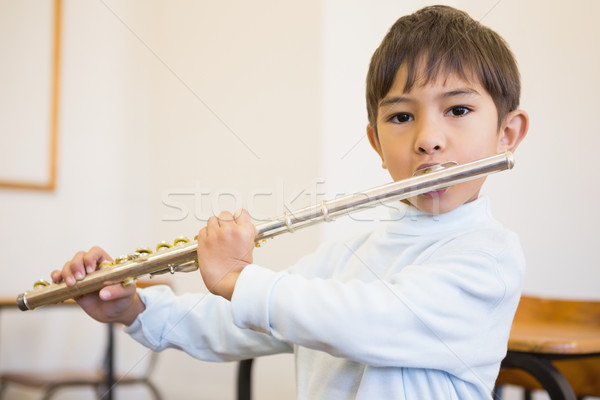 Cute pupil playing flute in classroom  Stock photo © wavebreak_media