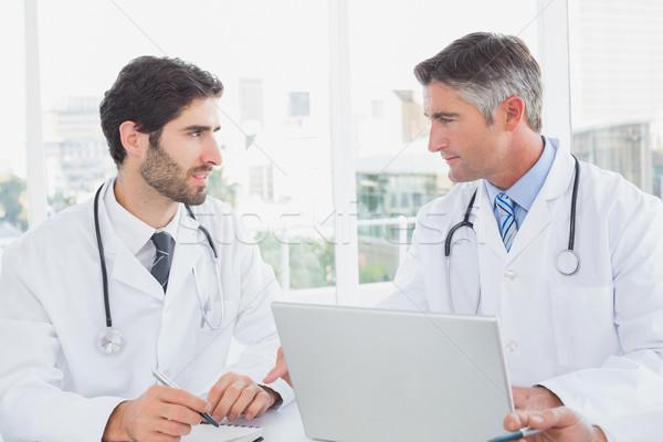 Doctor sitting and taking notes Stock photo © wavebreak_media