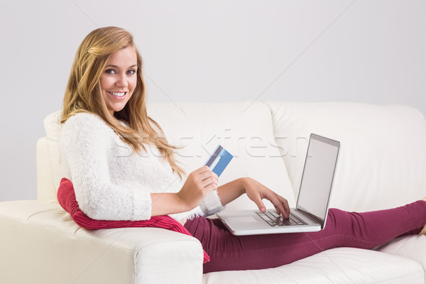 Pretty blonde relaxing on sofa with laptop Stock photo © wavebreak_media