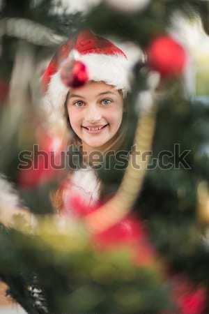 Festive litte girl decorating christmas tree Stock photo © wavebreak_media