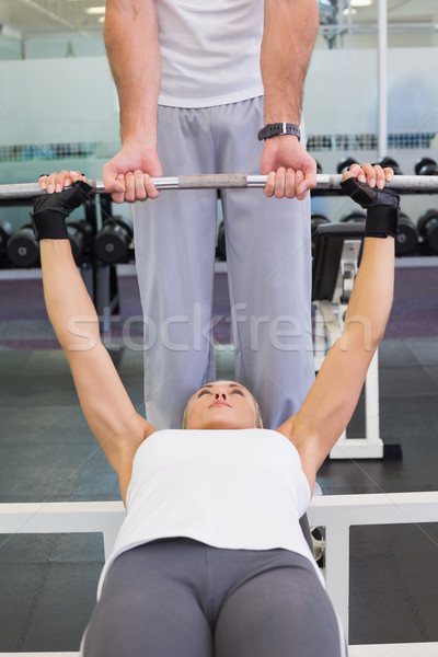 Trainer helping woman with lifting barbell in gym Stock photo © wavebreak_media