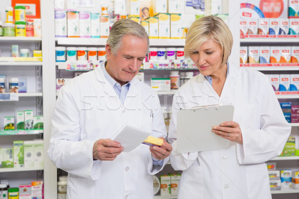 Stock photo: Smiling pharmacists team talking about medication