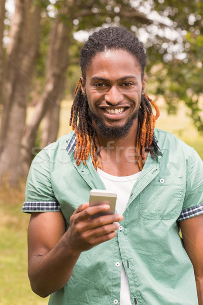 Happy young man using smartphone Stock photo © wavebreak_media