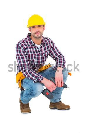 Crouching handyman holding power drill Stock photo © wavebreak_media