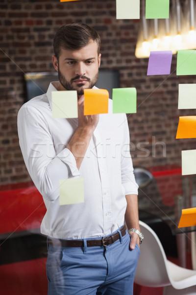 Casual empresario mirando notas adhesivas oficina ventana Foto stock © wavebreak_media
