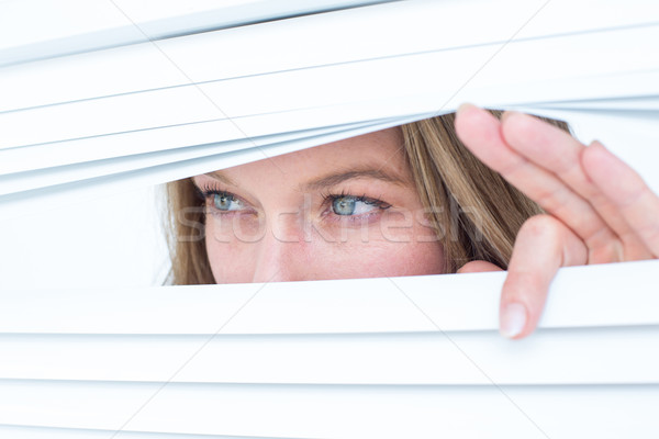 Woman peering through roller blind Stock photo © wavebreak_media