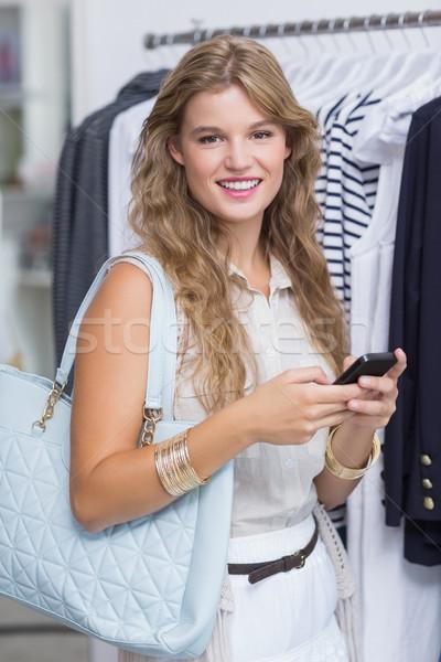 Csinos mosolyog szőke nő néz okostelefon ruházat Stock fotó © wavebreak_media