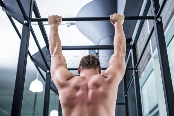 Back view of muscular man doing pull ups Stock photo © wavebreak_media