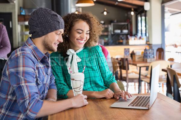 Happy friends using laptop at table in restaurant Stock photo © wavebreak_media